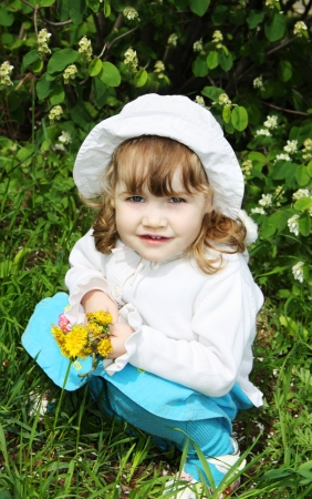 hunker: Beautiful little girl wearing white panama holds yellow dandelions and sits on grass Stock Photo