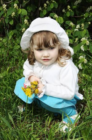 hunker: Beautiful little girl wearing white hat with yellow dandelions sits on grass and looks into distance