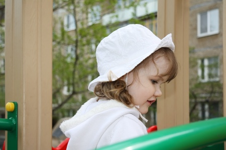 Beautiful little girl wearing white blouse plays at playground photo