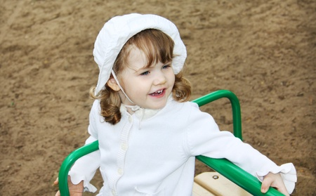 Happy cute girl wearing white hat rides on small carousel at playground photo