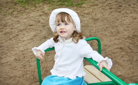 playground rides: Llittle girl wearing white hat rides on small carousel at playground