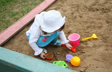 Llittle girl wearing white hat plays in sandbox at playground, top view photo