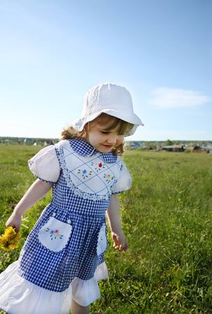 Happy little girl wearing dress and white hat walks on green field photo