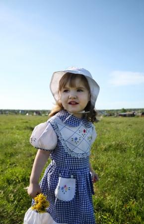 Happy little girl wearing dress looks into distance on green field photo