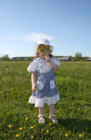 Happy little girl wearing dress hides her face in yellow dandelions on green field near village photo