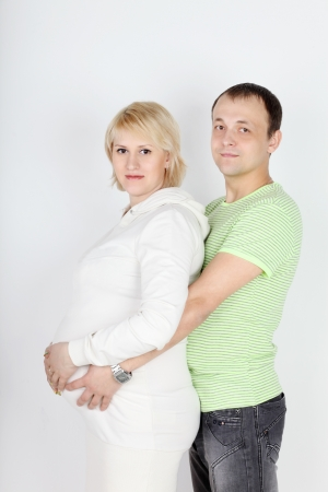 Happy pregnant wife in white and husband hold belly on white background  photo