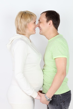 Happy pregnant wife and husband touch each other noses and laugh on white background  photo