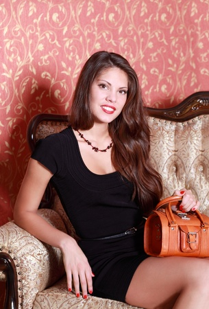 Beautiful smiling girl in short black dress with handbag sits on vintage couch. Stock Photo - 20945909