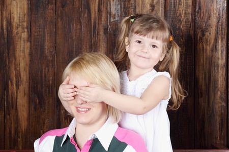 closes eyes: Beautiful little girl in white dress closes eyes to her mother.