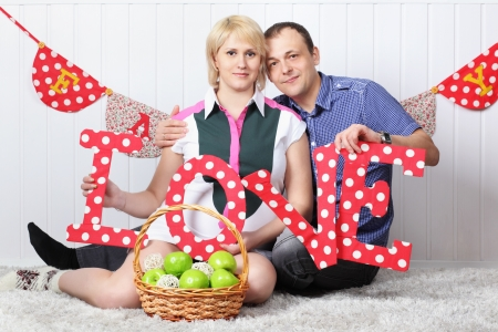 Happy pregnant wife and husband sit on carpet and hold letters L O V E. photo