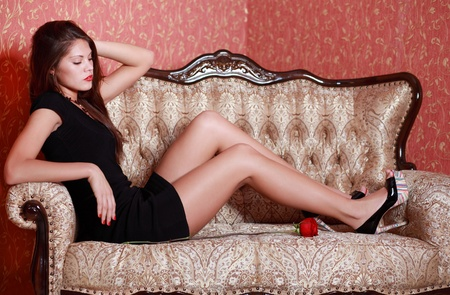Beautiful girl in short black dress with red rose sits on vintage couch and looks down. photo