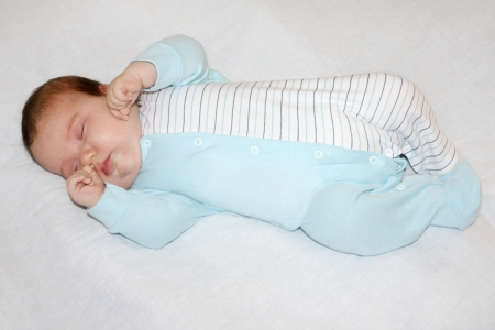 Little cute baby in blue jumper sleeps on white sheet on bed. photo