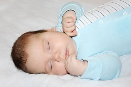 Little beautiful baby in blue jumper sleeps on white sheet on bed. photo