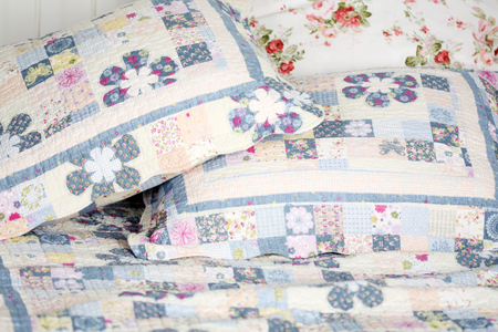 double bed: Beautiful and soft colored pillows lie on double bed with blanket.