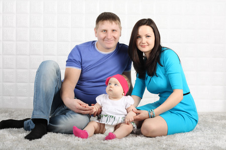 Happy young father, mother and baby sit on soft grey carpet. photo