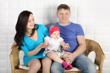 Young father, beautiful mother and cute baby sit on wicker\ sofa at home.