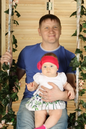 Happy father with cute baby sits on swing overgrown with green ivy. Stock Photo - 22273636