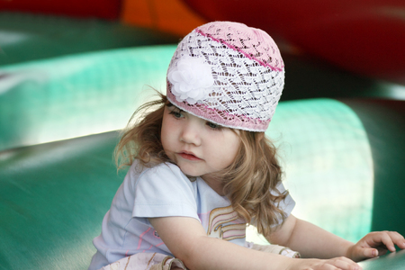 Little beautiful girl in openwork hat on green inflatable trampoline. photo