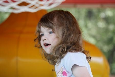 brincolin: Ni�a muy feliz en amarillo trampol�n inflable mira hacia otro lado. Foto de archivo