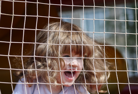 Little beautiful happy girl shouts in green playground with grid. photo