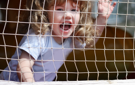 Little beautiful happy girl shouts at playground with grid. photo