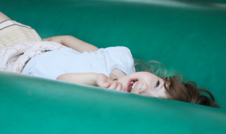 Little beautiful happy girl lies on green bouncy castle and laughs. photo