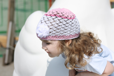 face centered: Little happy girl in white hat with curly hair looks away at sunny day.