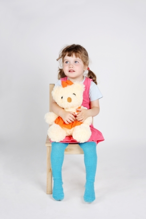 Little cute girl sits at wooden chair with toy bear and looks away on grey background. photo