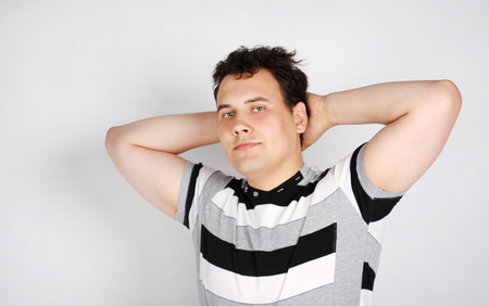Brunet man in striped T-shirt smiles and stretches oneself on grey background. photo