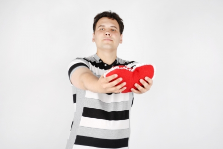 Suffering handsome man gives red soft heart on grey background. Focus on heart. photo
