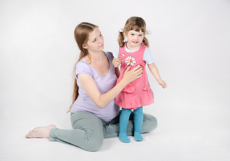 Pregnant woman sits on floor near little smiling daughter on grey background. photo