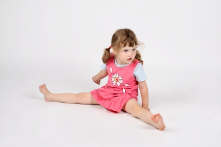 little girl barefoot: Little surprised barefoot girl in pink sits on floor and looks away on white background.