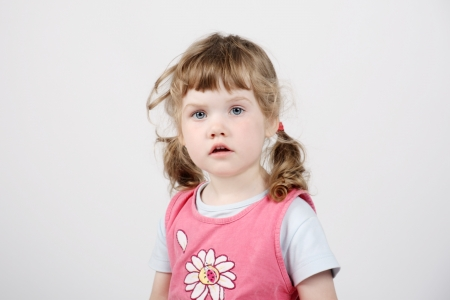 Little beautiful girl in pink looks at camera on white background. photo
