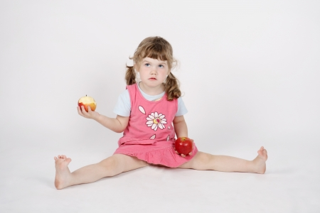 Little beautiful girl eats apple and holds second apple on floor in hand on white background. photo