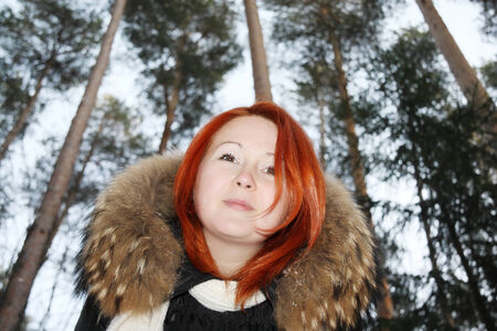 Happy redhead girl looks at camera in pine forest at winter. photo