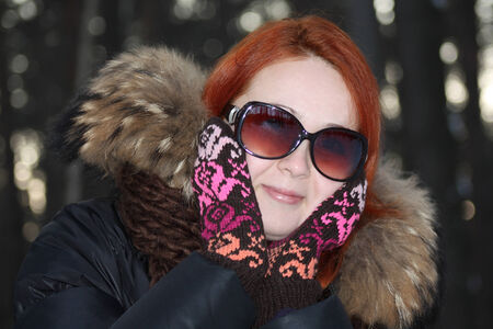Happy girl in mittens and sunglasses looks away in forest at winter. photo