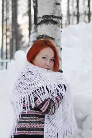 Pretty girl in jacket and white shawl stands near tree and huge snowdrift at winter. photo