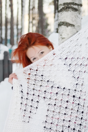 Redhead girl hides her face behind shawl near birch at winter day. photo