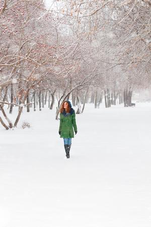Pretty girl in green overcoat walks outdoor at winter day in park Standard-Bild