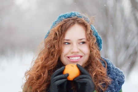 Beautiful girl in blue beret holds mandarin and looks away at winter day in park photo