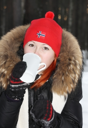 Happy girl in red hat drinks hot tea and looks at camera in forest at winter. photo