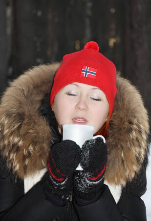 Happy girl in red hat drinks hot tea and dreams with closed eyes in forest at winter. photo
