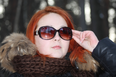 Happy redhead girl in warm clothes and sunglasses looks away in forest at winter. photo