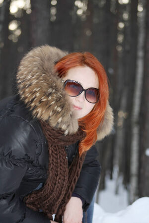Happy girl in clothes with fur and sunglasses smiles in forest at winter. photo