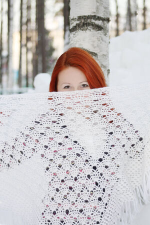 Pretty girl hides her face behind shawl near tree and huge snowdrift at winter. photo