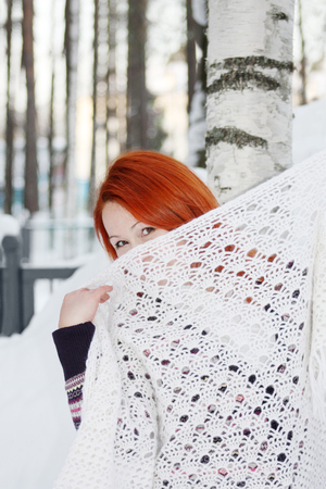 hides: Cute girl hides her face behind shawl near birch at winter forest. Stock Photo