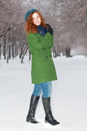 Pretty smiling girl in green overcoat poses outdoor at winter day in park photo