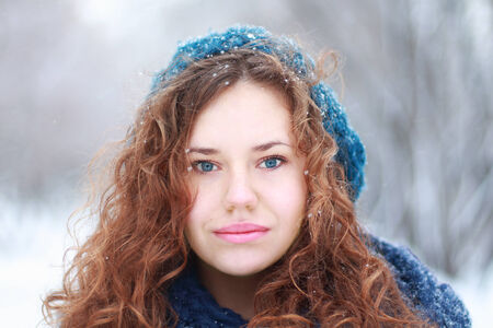 Beautiful girl in blue beret looks at camera outdoor at winter day in park photo