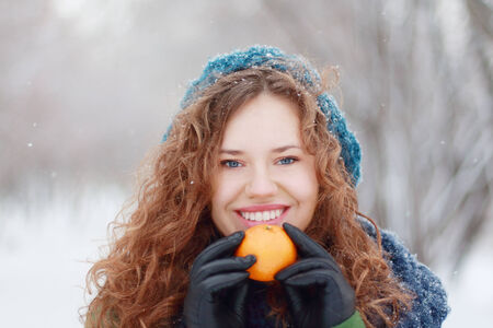 Beautiful girl in blue beret holds mandarin and smiles outdoor at winter day in park photo