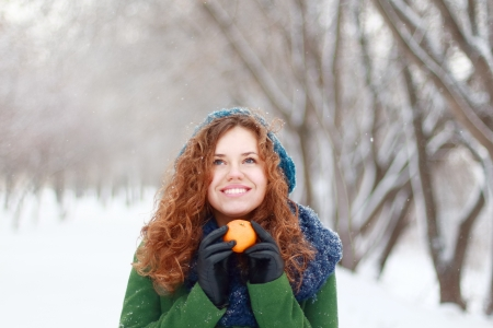 Beautiful girl in blue beret holds mandarin and looks up at winter day in park photo